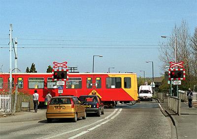 'A Tyne & Wear Metrotrain crosses a level crossing at Kingston Park', 2001, SPSmiler